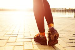 Female runner feet running at sunrise. Woman legs running in the rays of sun. Female runner feet running at sunrise closeup on shoes. Girl fitness jog workout Royalty Free Stock Photo