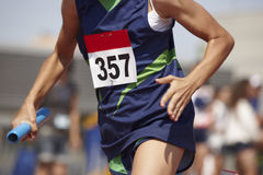 Female runner finalizing a relay race in a running track Stock Photo