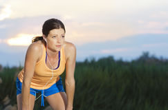 Female Runner finishing a run. A tired exhausted woman resting after a long hard run Stock Photo