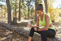 Female runner in a forest sits checking her smartwatch Stock Image