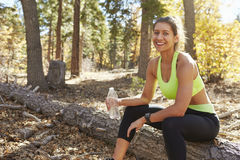 Female runner in a forest takes a break, looking to camera Stock Images
