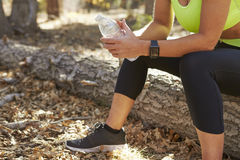 Female runner in a forest takes a break, low section crop Stock Photo