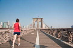 Female runner going though Brooklyn Bridge. A person running through Brookly Bridge royalty free stock photo