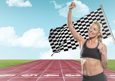 Female runner with hand in air on track against sky and checkered flag Royalty Free Stock Image