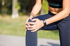 Female runner holding aching knee at jogging. Female runner holding aching knee at morning jogging. Sport injury concept background stock images