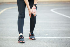 Female runner is holding her injured leg. Royalty Free Stock Photography