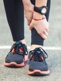 Female runner is holding her injured leg. Royalty Free Stock Photos