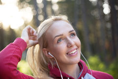 Female runner in hoody is jogging in nature Stock Photo