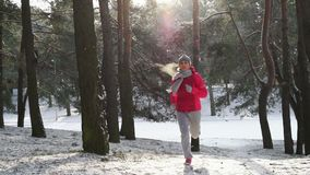 Female runner jogging in cold winter forest wearing warm sporty running clothing and gloves. Running sport woman. Female runner jogging in cold winter forest stock footage
