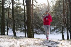 Female runner jogging in cold winter forest wearing warm sporty running clothing and gloves. royalty free stock image