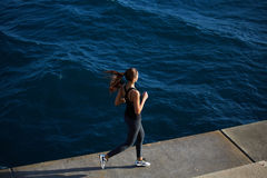 Female runner jogging next to the ocean Stock Images