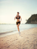 Female runner jogging during outdoor workout on beach Stock Image