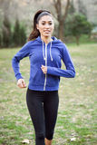 Female runner jogging during outdoor workout in a park. Stock Photos