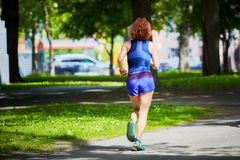 Female runner jogging in a park royalty free stock images