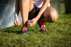 Female runner lacing sport and running shoes. Female runner lacing running shoes and getting ready for training. Woman tying sport footwear laces before Royalty Free Stock Photo