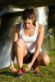 Female runner lacing sport shoes before running Stock Photo