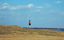 Female Runner at the Lake. A female runner exercises alongside the shoreline of a suburban lake Royalty Free Stock Photography