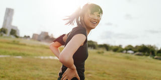 Female runner laughing on field in morning. Shot of fitness young woman standing outdoors looking at camera and laughing. Female runner on field in morning stock photos