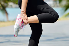 Female runner leg and muscle pain during running outdoors Stock Image