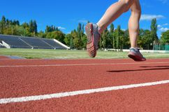 Female runner legs in shoes on stadium track, woman athlete running and working out outdoors, sport and fitness. Concept stock photos