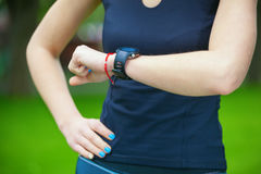 Female runner looking at her sport watch. Royalty Free Stock Photo