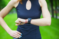 Female runner looking at her sport watch. Royalty Free Stock Image