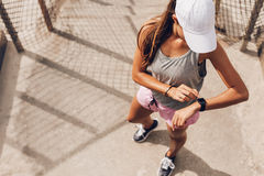 Female runner looking at smart watch heart rate monitor. Young woman checking progress on smart watch. Female runner looking at smart watch heart rate monitor Royalty Free Stock Photography