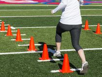 Runner steping over orange cones for speed training Royalty Free Stock Photography