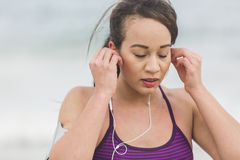 Female runner preparing for outdoor workout on the beach setting Stock Image