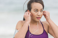 Female runner preparing for outdoor workout on the beach setting Royalty Free Stock Image