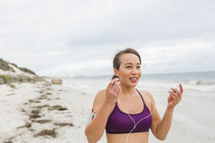Female runner preparing for outdoor workout on the beach setting up earphones Royalty Free Stock Images