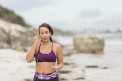 Female runner preparing for outdoor workout on the beach setting up earphones Royalty Free Stock Photos