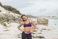 Female runner preparing for outdoor workout on the beach setting up earphones Stock Photography