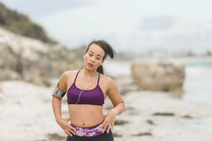 Female runner preparing for outdoor workout on the beach setting up earphones Stock Photo