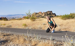 Female runner ready for a morning jog. A female runner stops to tie shoes before a morning run on a along a desert pathway Royalty Free Stock Photo