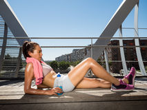 Female runner relaxed lying and resting after making a big effort. Recovery and hydration concept royalty free stock photography