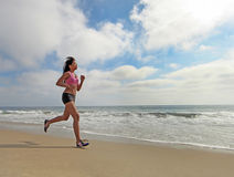 Female Runner Running at the Beach Jogging Stock Images