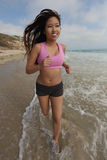 Female Runner Running at the Beach Jogging Stock Photo
