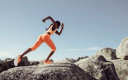 Female runner running over big rocks. African woman running over big rocks at the beach. Female runner sprinting over rocks outdoors stock photography