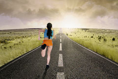 Female runner running at road Stock Images