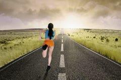 Female runner running at road Stock Images