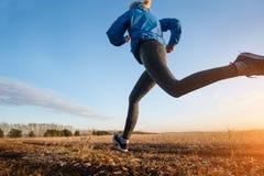 Female runner running on a rural road during sunset. Stock Images