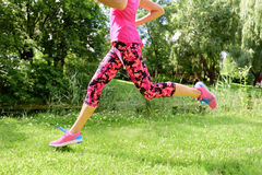 Female runner running shoes and legs in city park. Woman jogging wearing floral capris leggings compression tights and pink running shoes stock photography
