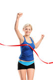 Female runner running towards a finish line. A view of a female runner running towards a finish line isolated against white background Royalty Free Stock Photos