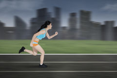 Female runner running on a track. Photo of a young woman running on a track while wearing sportswear Royalty Free Stock Image