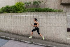 Female runner running uphill on town street. Sporty young woman doing cardio exercises outdoors. Female runner running uphill on town street. Sporty young woman Stock Image