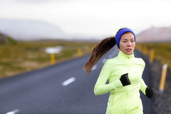 Female runner running in warm clothing outside. Female runner running in warm clothing for winter and autumn outside. Woman runner training in cold weather Stock Images