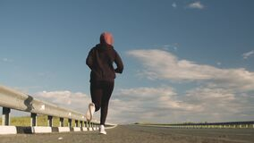 A female runner runs along the track, training in the open air, view from below. A girl runs along the side of the road