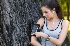 Female runner settings smart phone in armband Stock Photo
