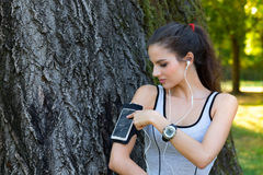 Female runner settings smart phone in armband Stock Image